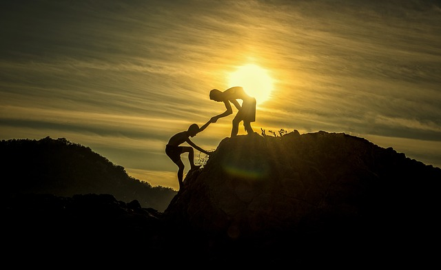 one boy helping another boy uphill and sun in background to show cooperation