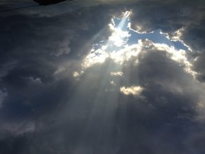 sun rays through dark clouds to show hope and God's grace